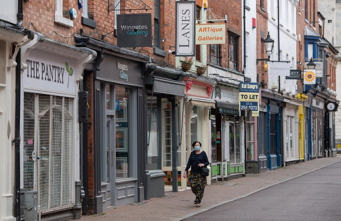 England, Leicester: A woman wearing a face mask walks in front of closed shops at a deserted street where localised coronavirus lockdown restrictions have been in place since 29 June, people were urged not to travel in or out of the area. Photo: Joe Giddens/PA Wire/dpa