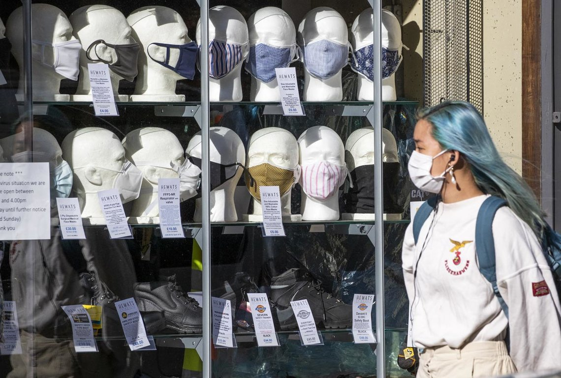 22 September 2020, Scotland, Edinburgh: A woman wearing a protective face mask walks past a shop selling masks in Edinburgh city centre, after First Minister Nicola Sturgeon announced a range of new measures to combat the rise in coronavirus cases in Scotland. Photo: Jane Barlow/dpa.