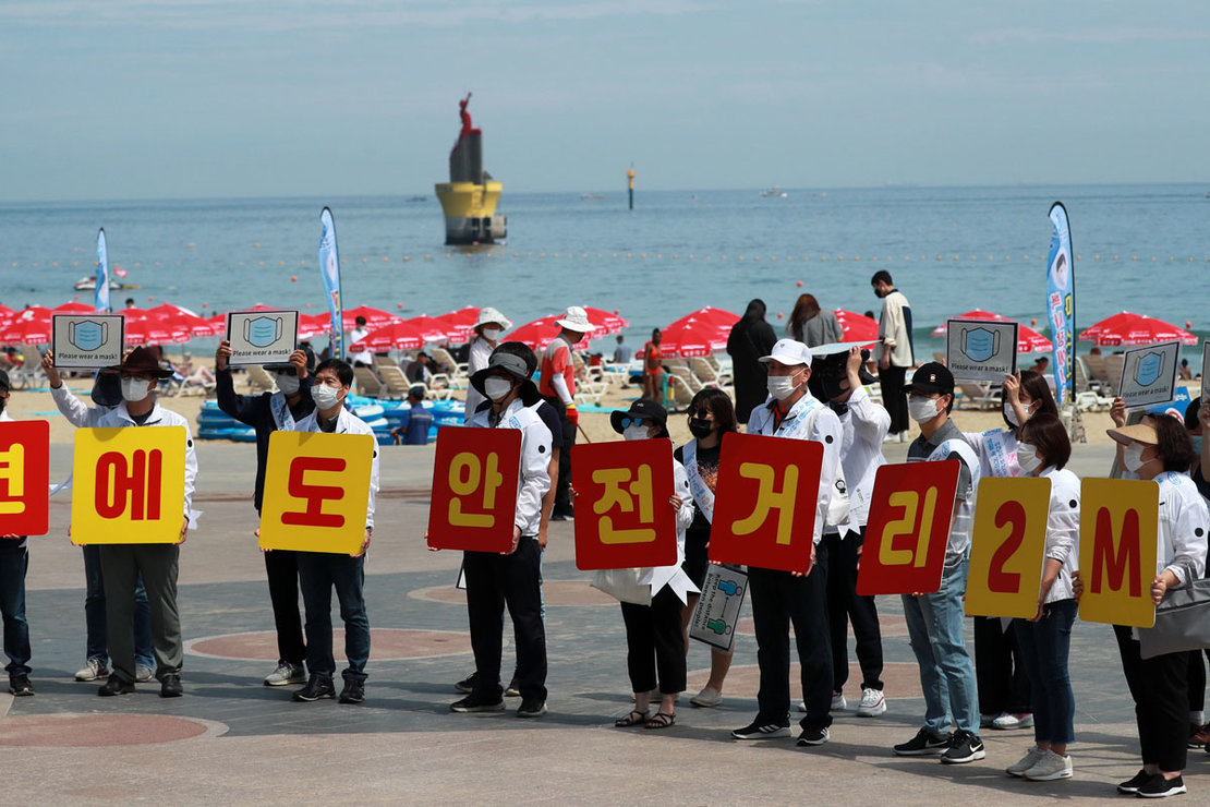 South Korea: Officials at the southeastern port city of Busan hold signs reminding visitors at Haeundae Beach to keep a 2-meter distance, to prevent the spread of the Corona virus. Photo: YNA/dpa.