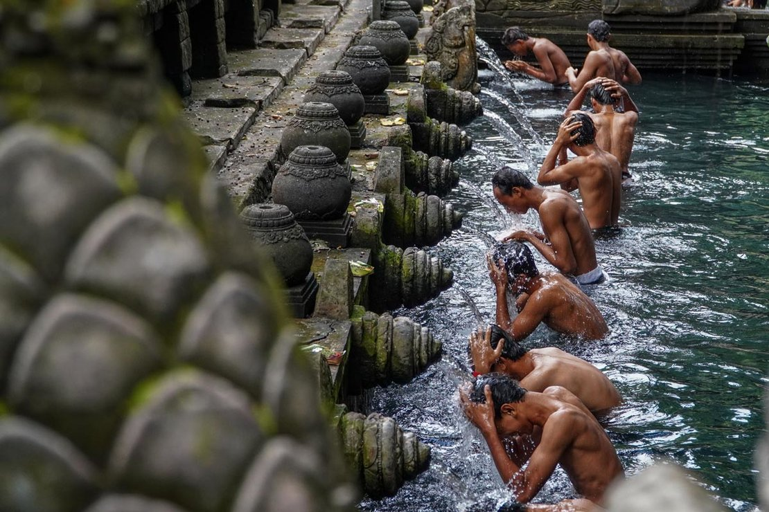Indonesia. Men wash their bodies at the holy spring shower during the Banyu Pinaruh cleansing ceremony at Tirta Empul Temple. Photo: Dicky Bisinglasi/dpa