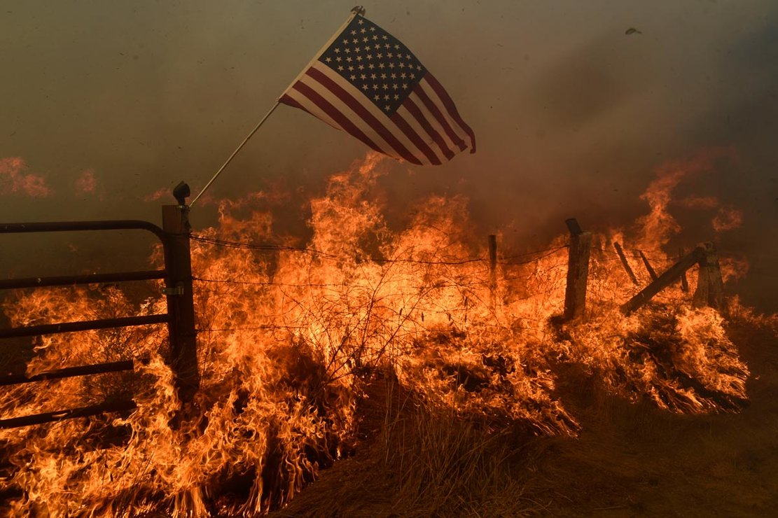 A US flag flies above a fire on an area in southern Santa Clara County during the spread of forest fires. Photo: Neal Waters/ZUMA Wire/dpa