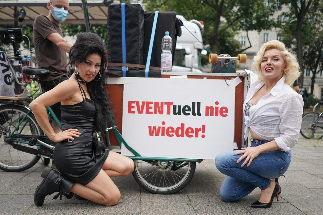 "Berlin: Rachel (L) and Suzy, two performers from the Estrel Hotel, kneel next to a poster saying ""Possibly never again"" during a demonstration calling for more support for the culture and event industry during the coronavirus (COVID-19) pandemic. Photo: Jörg Carstensen/dpa"