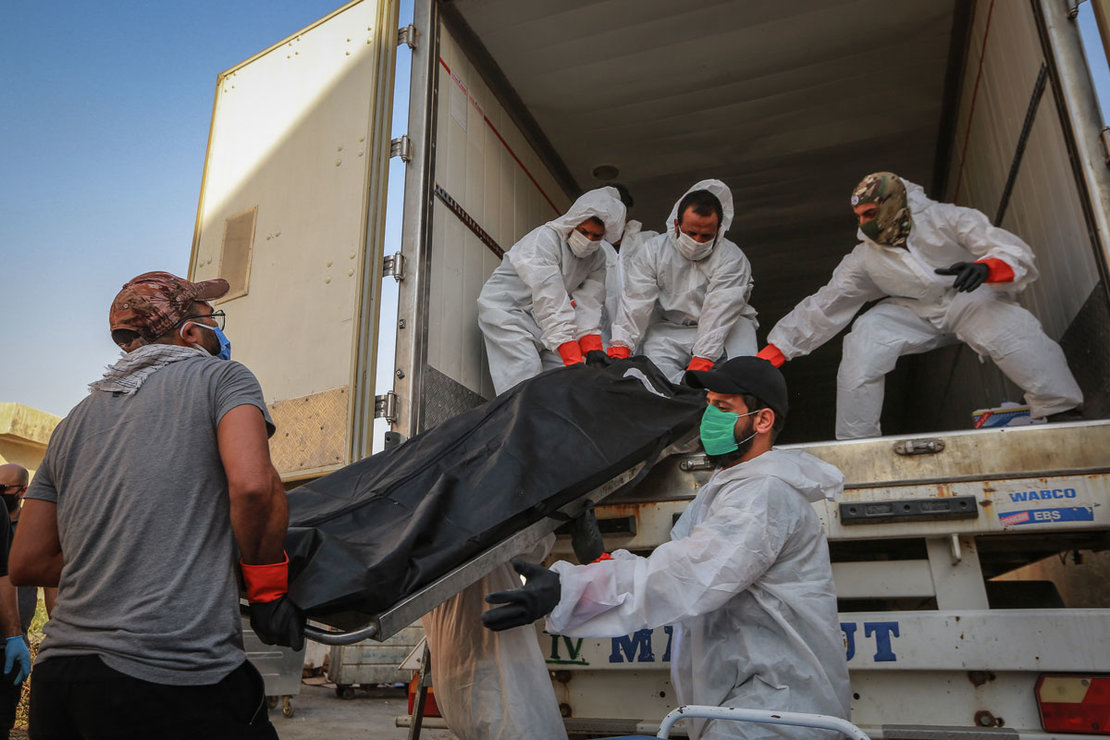 Iraq: Workers wearing full protective gear load bodies of people who died due to the coronavirus, into a refrigerator truck of the Popular Mobilization Forces (PMF) to be transferred from Baghdad to Wadi Al-Salam Cemetery in the city of Najaf. Photo: Ameer Al Mohammedaw/dpa