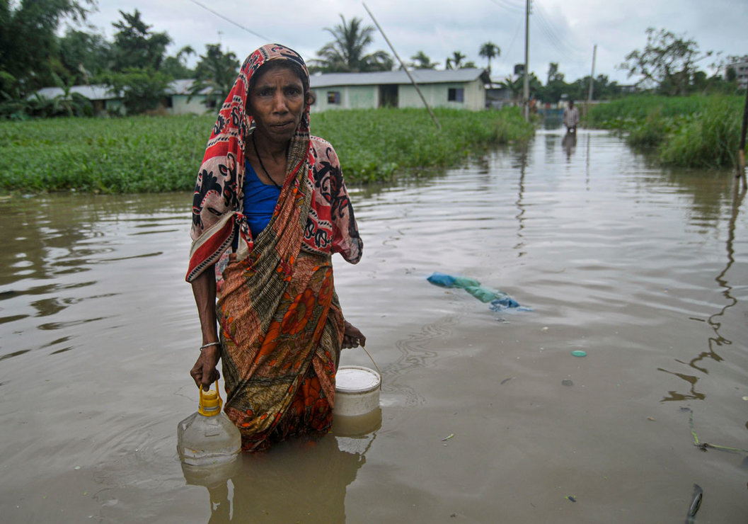 Bangladesh, Sylhet: A women walks in a flooded road after collecting drinking water through a flooded road at Sadarpur area following heavy rainfall triggered by monsoon over the last few days. Photo: Md Rafayat Haque Khan/dpa