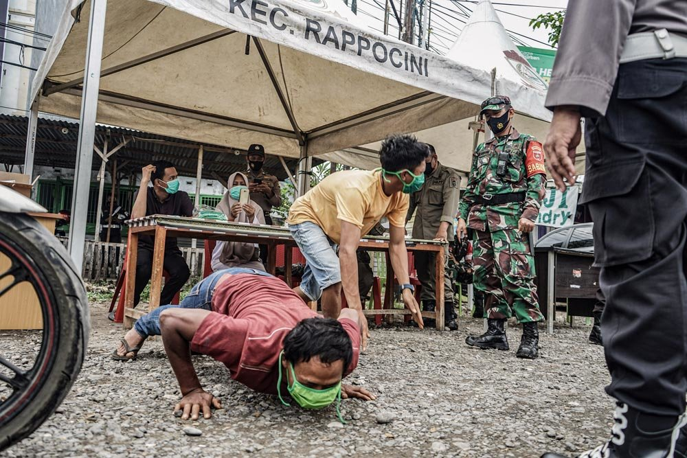Indonesia, Makassar: A motorist drops down and gives push ups in front of a member of the military as a punishment for entering the city of Makassar without carrying a COVID-19 free certificate. Photo: Herwin Bahar/ZUMA Wire/dpa