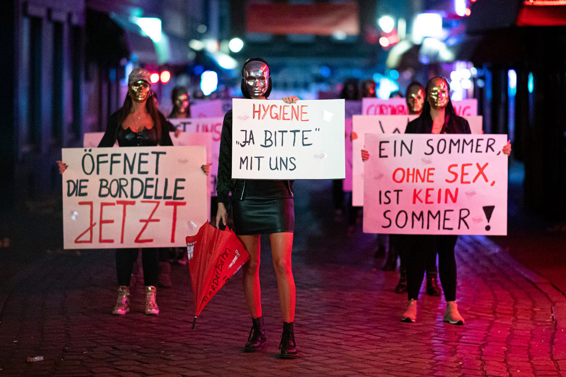 28 July 2020, Hamburg: Sex workers hold signs and placards during a demonstration in Herbertstrasse against the lockdown of the brothels due to the spread of the coronavirus (COVID-19) pandemic. Photo: Daniel Reinhardt/dpa