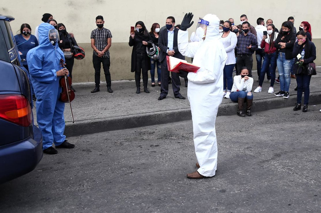 05 August 2020, Colombia, Bogota: A priest in protective clothing speaks during a funeral service for a coronavirus victim at a street. Photo: Álvaro Tavera/dpa.