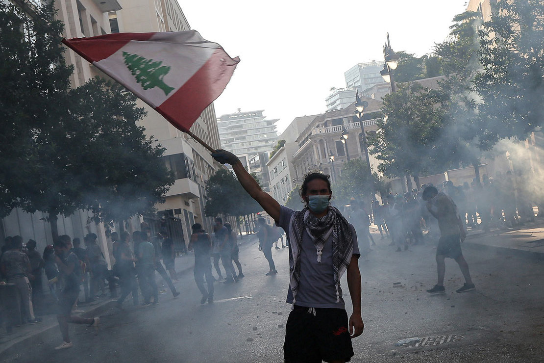 10 August 2020, Lebanon, Beirut: An anti-government activist flies the Lebanese national flag during clashes with riot police in Beirut's downtown. The Lebanese government resigned following the massive Beirut port explosion of 04 August which killed at least 158 people, wounded 6000 and displaced some 250,000 to 300,000. Photo: Marwan Naamani/dpa.