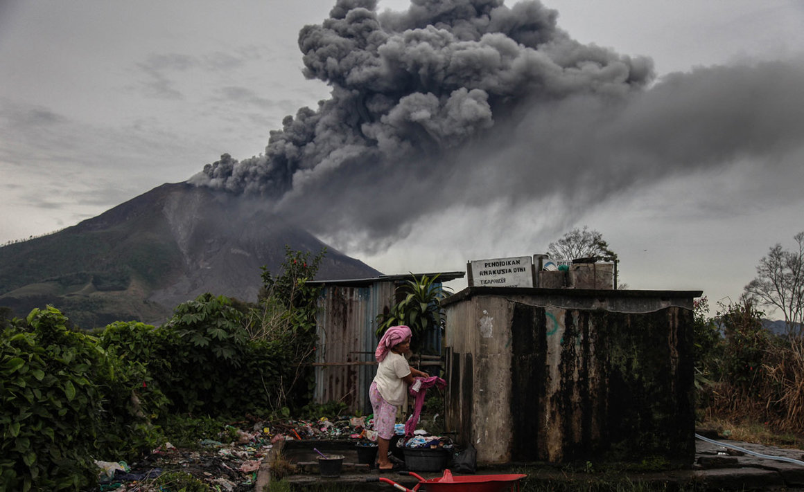 14 August 2020, Indonesia, Karo: A woman washes her clothes as Mount Sinabung Volcano spews thick ash and smoke into the sky following its recent eruption. Photo: Albert Ivan Damanik/dpa.