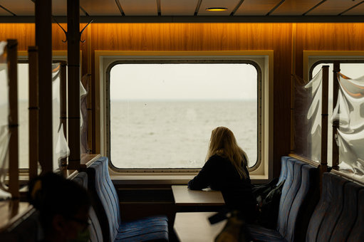 "dpatop - 22 February 2021, Lower Saxony, Norderney: A woman sits at a window of the ship during the crossing with the North Sea ferry Frisia from Norddeich to Norderney and looks at the North Sea (to dpa ""Tourism figures 2020 for Lower Saxony). Photo: Mohssen Assanimoghaddam/dpa"