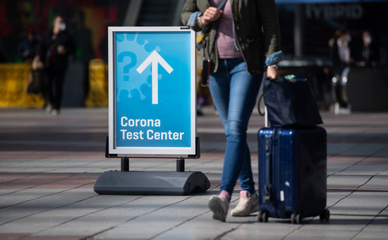 "26 March 2021, Bavaria, Munich: A woman passes past a sign with the inscription ""Corona Test Center"" at Munich airport. A new requirement for people arriving at German airports to have submitted to coronavirus testing has been postponed from Sunday to Tuesday. Photo: Sven Hoppe/dpa"