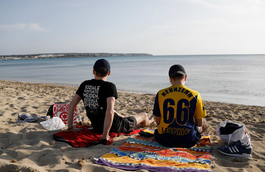 27 March 2021, Spain, Palma: German tourists from Leipzig Lucas and Marcel relax on the beach of Arenal. Photo: Clara Margais/dpa