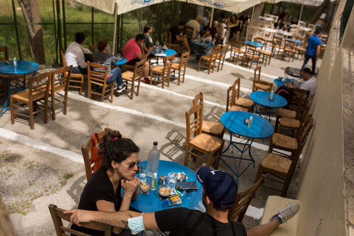03 May 2021, Greece, Athens: People sit in a cafe in the Monastiraki district with the Acropolis in the background. Greece relaxes the measures imposed because of the Coronavirus pandemic. Photo: Socrates Baltagiannis/dpa