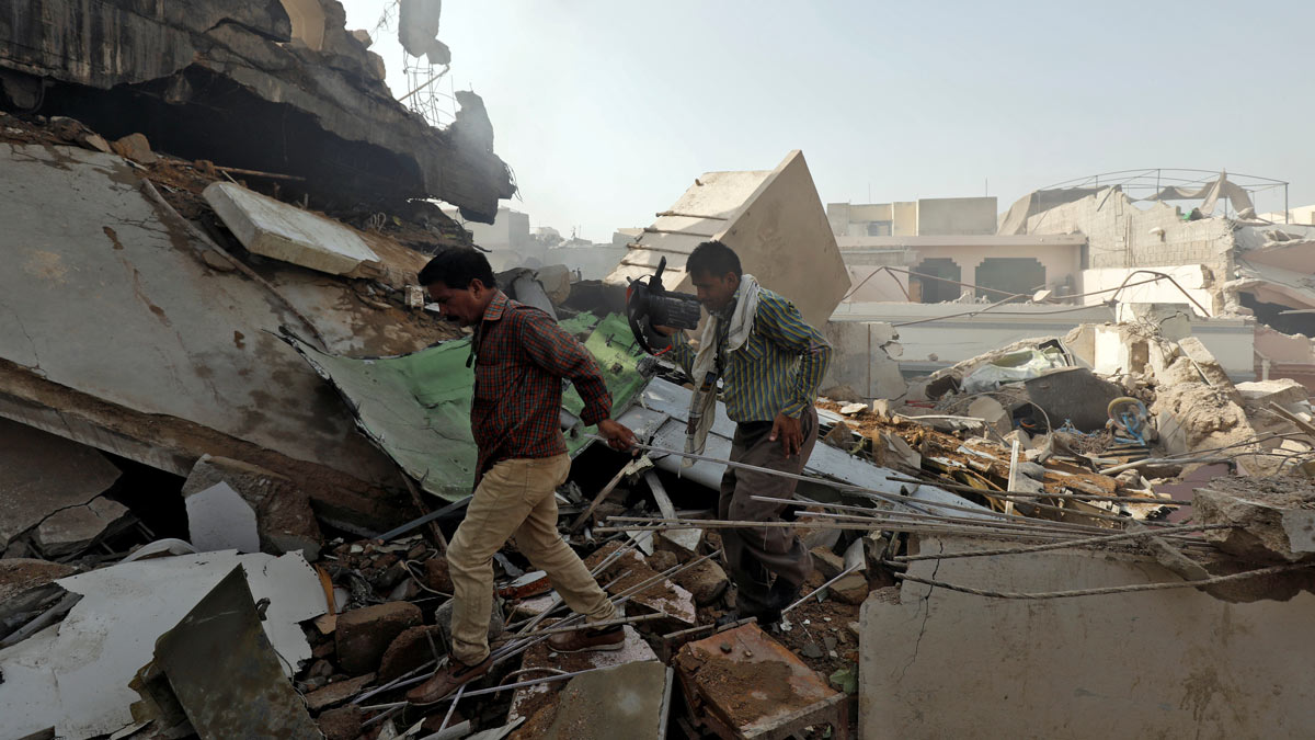 Men walk on the debris at the site of the plane crash in a residential area in Karachi. Photo: Reuters/Akhtar Soomro.