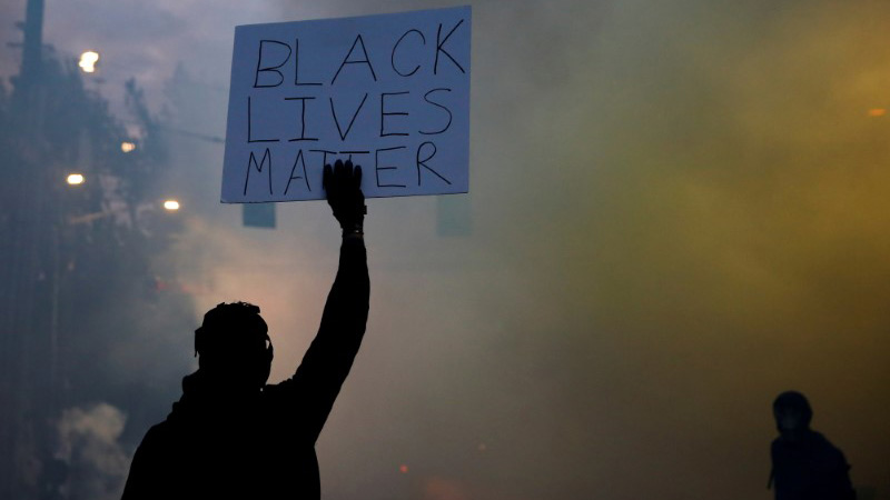 "A person holds a ""Black Lives Matter"" sign as a heavy cloud of tear gas and smoke rises after being deployed by Seattle police as protesters rally against police brutality and the death in Minneapolis police custody of George Floyd, in Seattle, Washington, U.S. June 1, 2020. Picture taken June 1, 2020. REUTERS/Lindsey Wasson"
