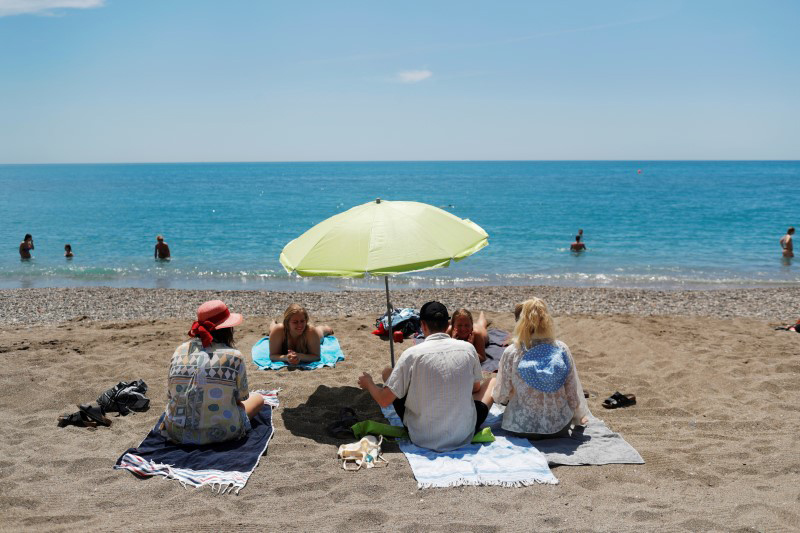File photo of people enjoying on La Malagueta beach, in Malaga (Spain). Photo: Jon Nazca/Reuters.