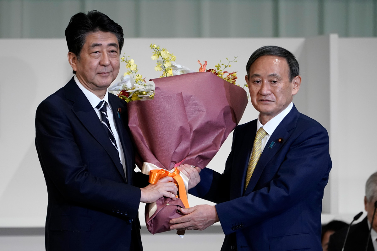 Former prime minister Shinzo Abe (L), presents a bouquet of flowers to his successor Yoshihide Suga. Photo: Pool/dpa.