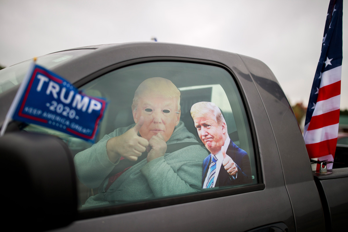 A man wears a mask of US President Donald Trump during cars parade to support Trump. Photo: Jeremy Hogan/dpa.
