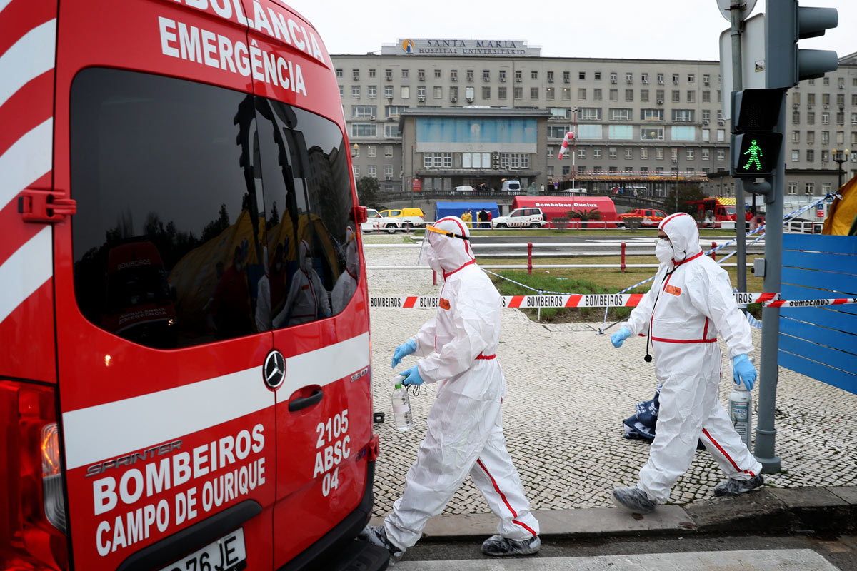 29 January 2021, Portugal, Lisbon: Health care workers in protective suits walk past an ambulance at the new triage center for coronavirus patients at Santa Maria Hospital. Photo: Pedro Fiuza/ZUMA Wire/dpa