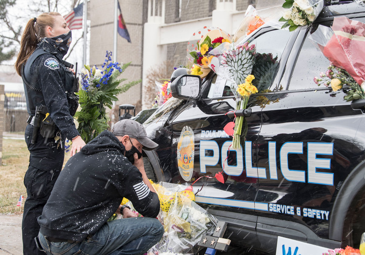 23 March 2021, US, Boulder: Policemen mourn near the vehicle of police officer Eric Talley, who was among the 10 people killed by a gunman during a mass shooting at the King Soopers grocery store. Photo: Pj Heller/ZUMA Wire/dpa