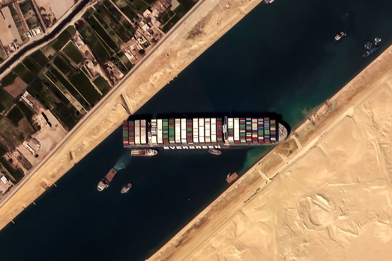 HANDOUT - 26 March 2021, Egypt, Suez: A satellite image provided by the European Space Imaging on 26 March 2021 shows the 'Ever given', a container ship operated by the Evergreen Marine Corporation, is currently stuck in the Suez Canal. The state-run Suez Canal Authority (SCA) announced that nearly 17,000 cubic meters of sand have been dredged around the ship after navigation through the Suez Canal has been temporarily suspended until the full refloating of the Panamanian massive cargo vessel which ran aground on Tuesday in the southern end of the Suez Canal and blocked the traffic in both directions. The ship turned sideways in the Canal, while on the route from China to Rotterdam, due to reduced visibility that resulted from a dust storm hitting the area, according to SCA. Photo: -/European Space Imaging/dpa - ATTENTION: editorial use only and only if the credit mentioned above is referenced in full